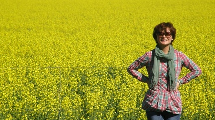 TJ standing in a field of canola flowers